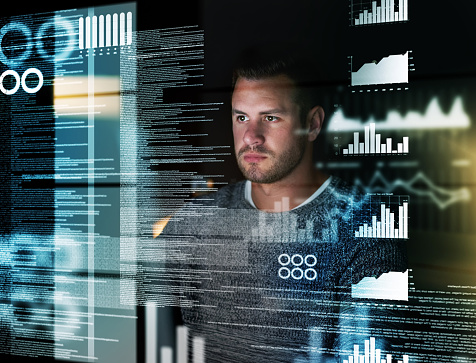 man looks at graphs and reports superimposed on glass