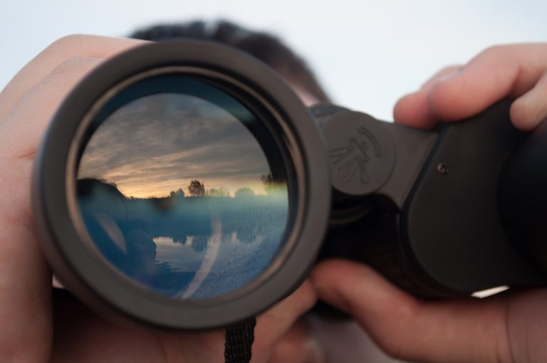 man looking through binoculars closeup