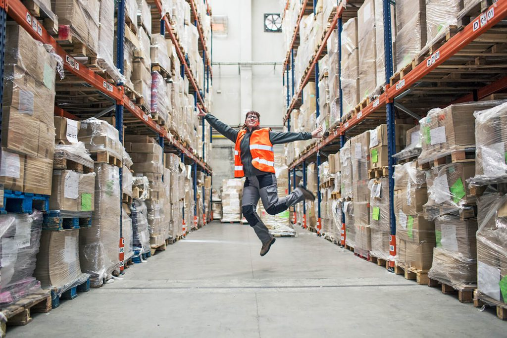 warehouse worker skips with joy inside warehouse