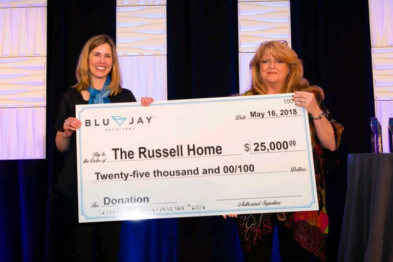 Two team members at The Russel Home holding a large donation check