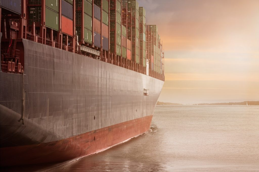 cargo ship with shipping containers leaving port