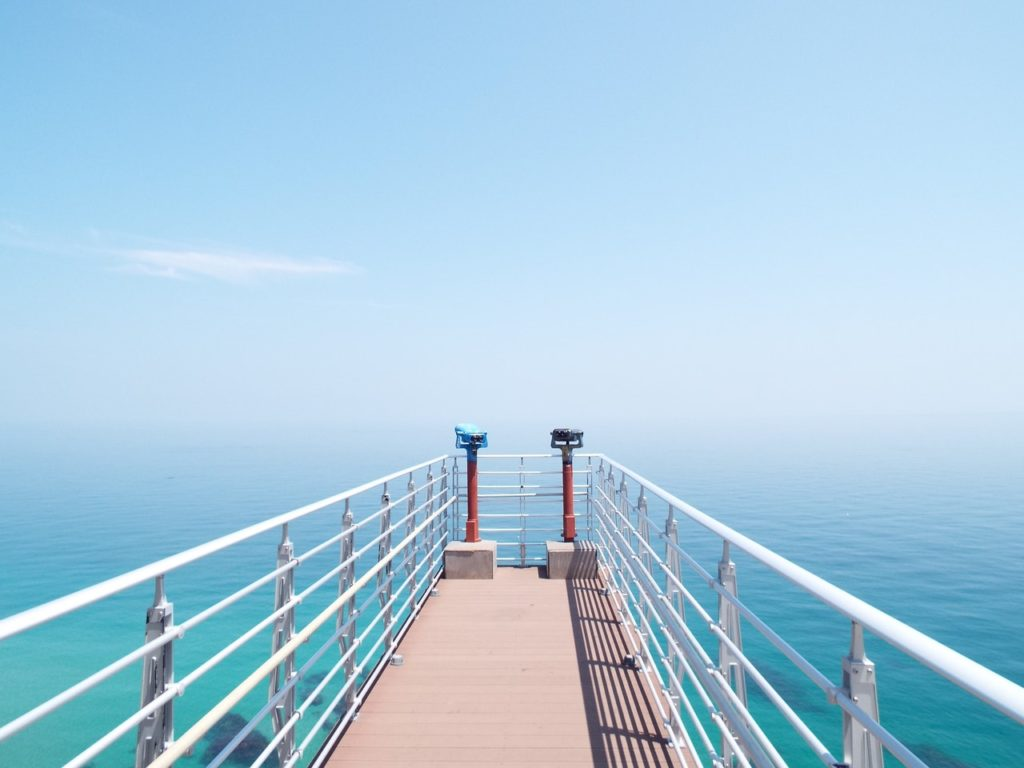 pier with viewfinders over a light blue ocean