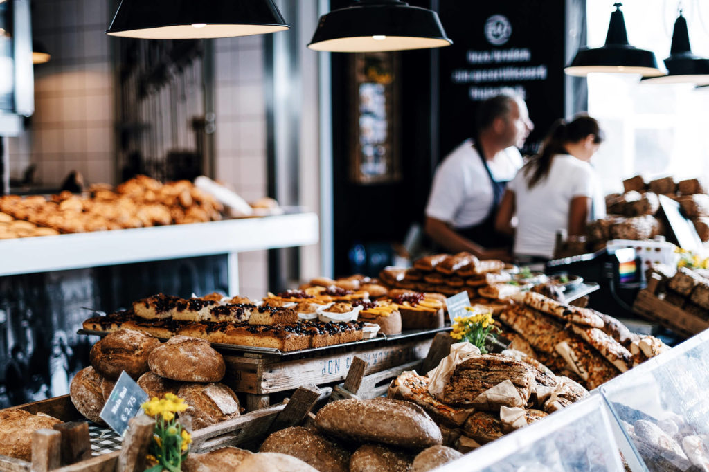 fresh baked breaks and other goods dispayed in a restaurant with two employees in the background