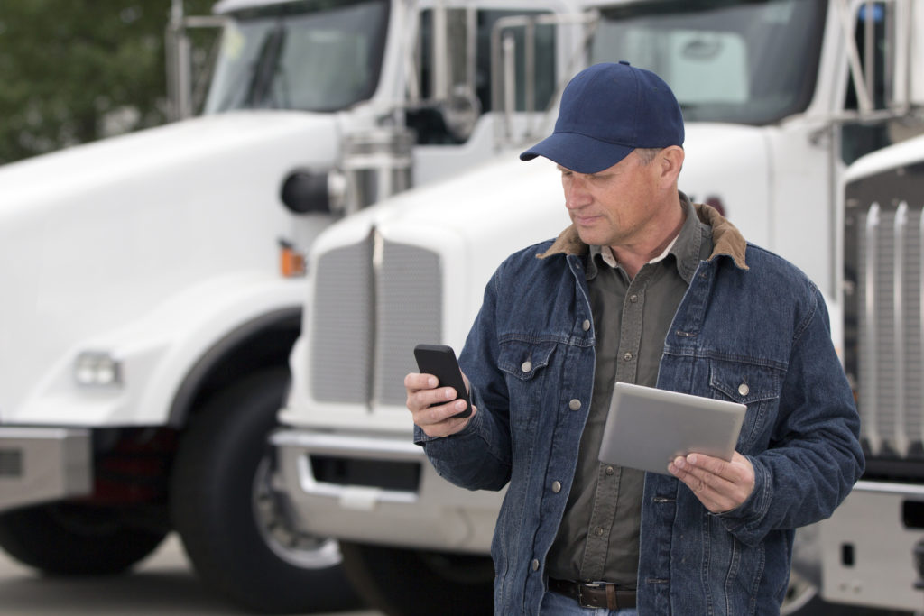 truck driver using cell phone and tablet at the same time