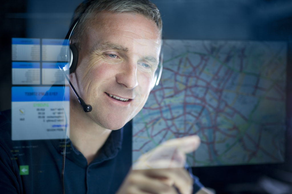 logistics operator smiling at map
