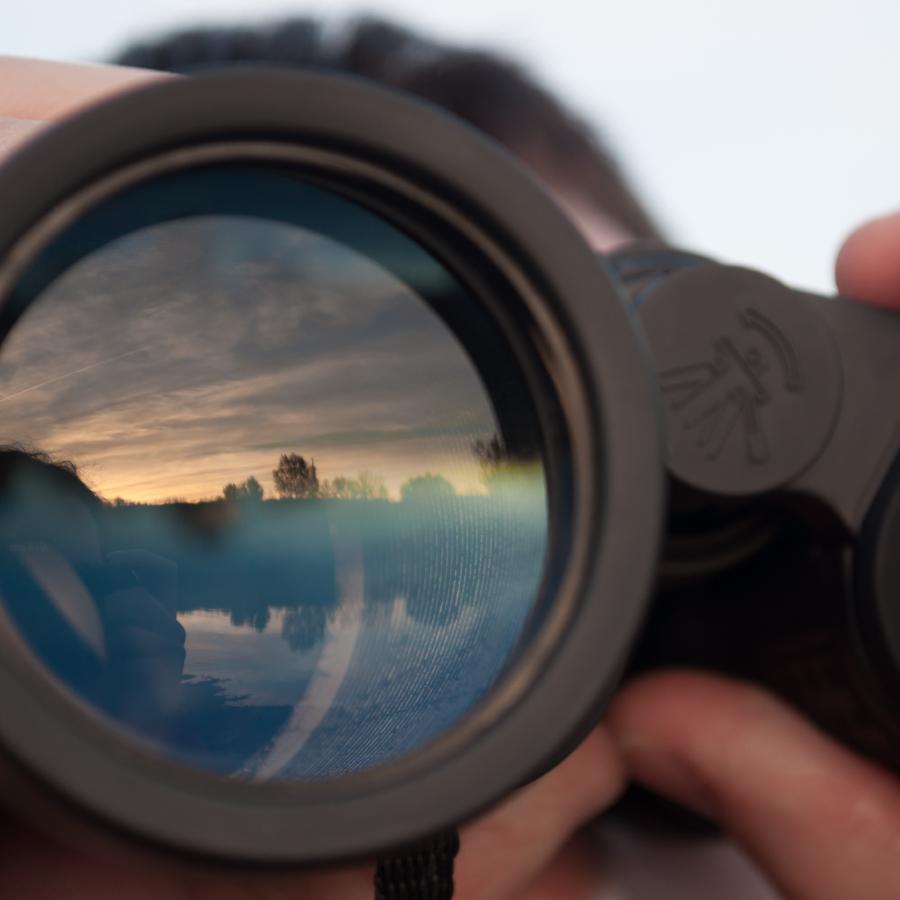 binocular lens being help up by man
