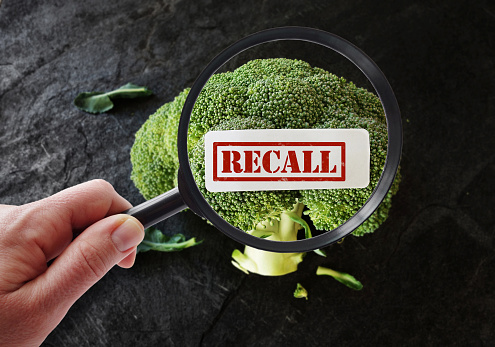 Hand with magnifying glass looking at broccoli Recall label