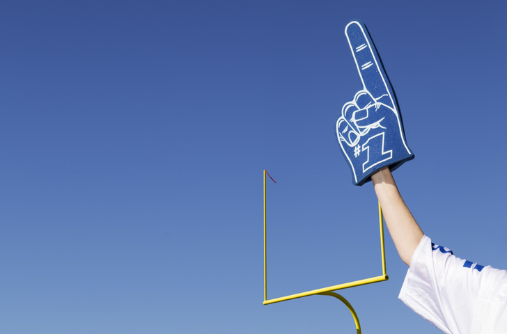 tailgating football fan with number one foam finger and stadium goal in the background
