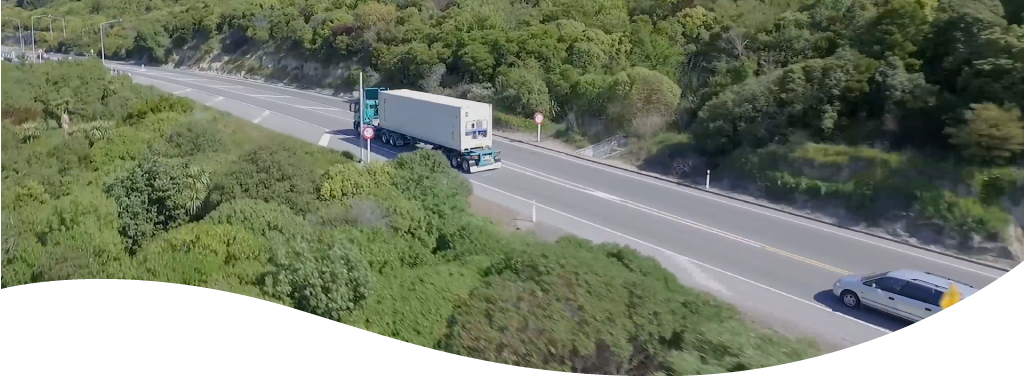 a semi truck diving down a wooded highway