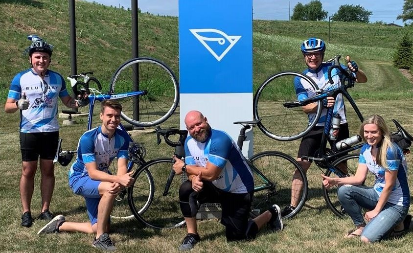 BluJay Solutions Cyclists Posing with Bicycles in Grass Outside