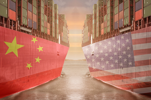 two ships loaded with shipping containers representing the USA and china trade war