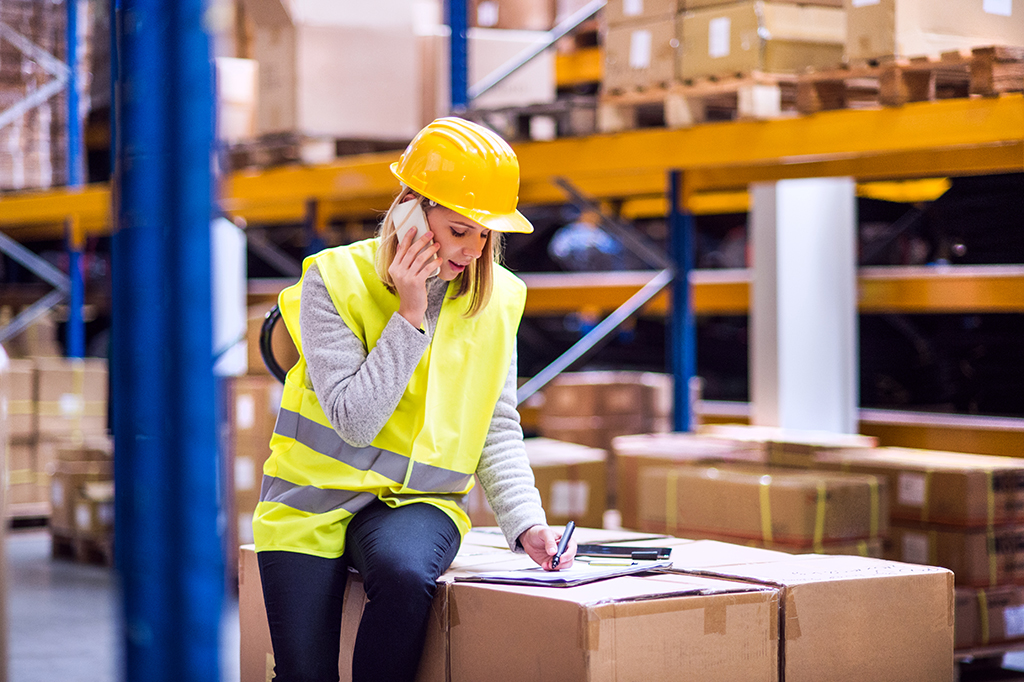 woman warehouse worker with smartphone and clipboard